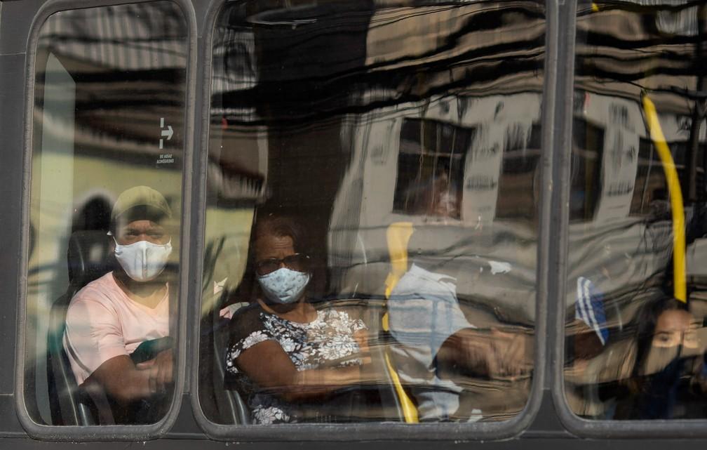 12 de maio - Passageiros de máscara olham pela janela de um ônibus durante o aumento das restrições na circulação para conter a propagação do novo coronavírus na área de Madureira, no Rio de Janeiro — Foto: Silvia Izquierdo/AP
