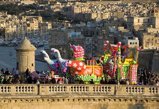 Um carro alegórico passa pelas muralhas da capital Valletta. Do outro lado do Grande Porto, as cidades fortificadas de Senglea e Cittá Vittoriosa (Foto: © Haroldo Castro/Época)
