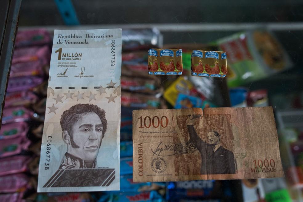 Nota de 1 milhão de bolívar venezuelano (esq), que equivale a 1.000 pesos colombianos (dir.), que vale o equivalente a dois temperos em uma loja de Puerto Concha, Venezuela — Foto: Federico Parra/AFP