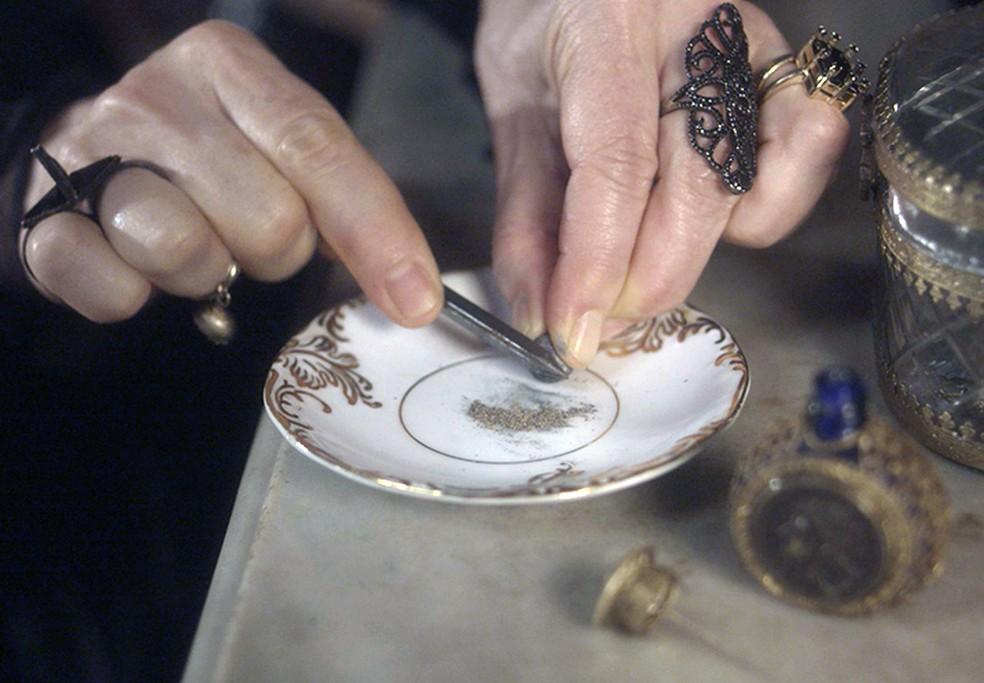 Depois de raspar, ela coloca o pó de chumbo em um vidrinho e guarda no decote (Foto: TV Globo)