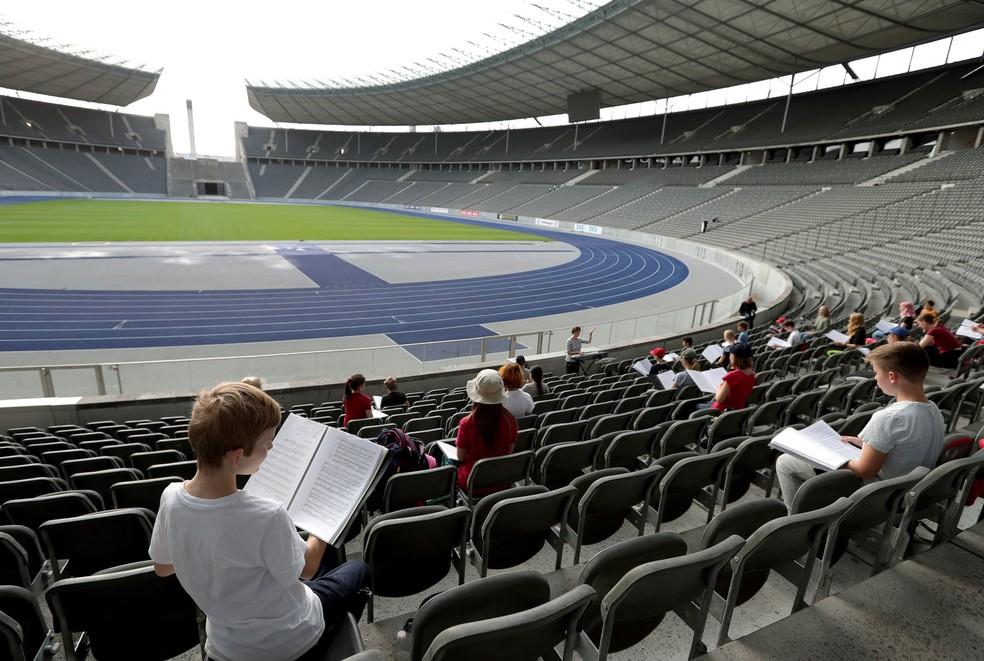 Devido às restrições do coronavírus e para manter a distância obrigatória entre os cantores, a ópera mudou ensaios para a arquibancada principal do Estádio Olympiuc em Berlim, na Alemanha. Foto do dia 23 de setembro — Foto:  Michael Sohn/AP