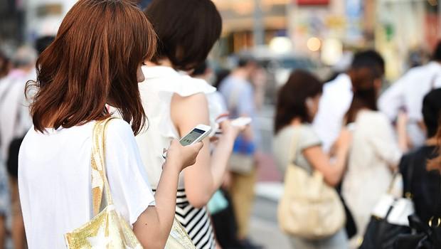 Jovens seguram celulares - smartphones - millenials - internet - móvel - dispositivos móveis (Foto: Atsushi Tomura/Getty Images)