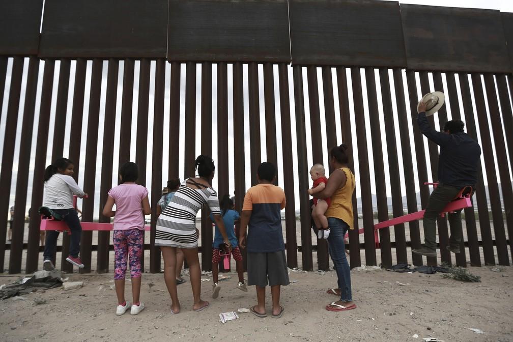 Mexicanos brincam na gangorra rosa montada na fronteira com os Estados Unidos na terça-feira (30), aqui vista do lado de Ciudad Juárez. — Foto: Christian Chavez/AP