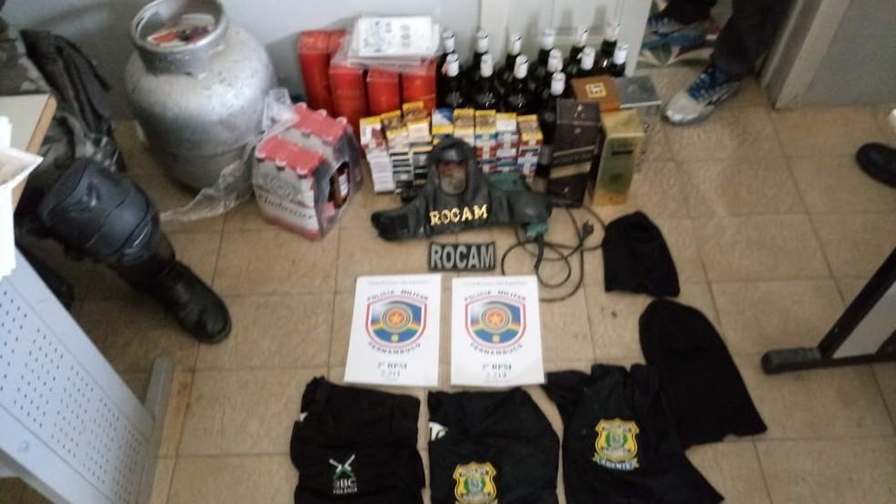 Camisas da polícia, armas, munição e produitos roubados de mercadinho em Lagoa do Carro, na Zona da Mata de Pernambuco, foram encontrados pelas Polícias Militar e Civil — Foto: Polícia Militar/Divulgação