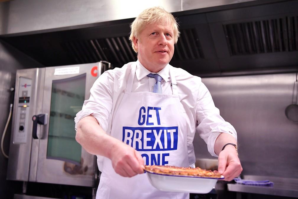 Boris Johnson prepara uma torta em uma cozinha em Derby, na Inglaterra, nesta quarta-feira (11), com um avental que diz 'realize o Brexit'. — Foto: Ben Stansall / AFP / Pool