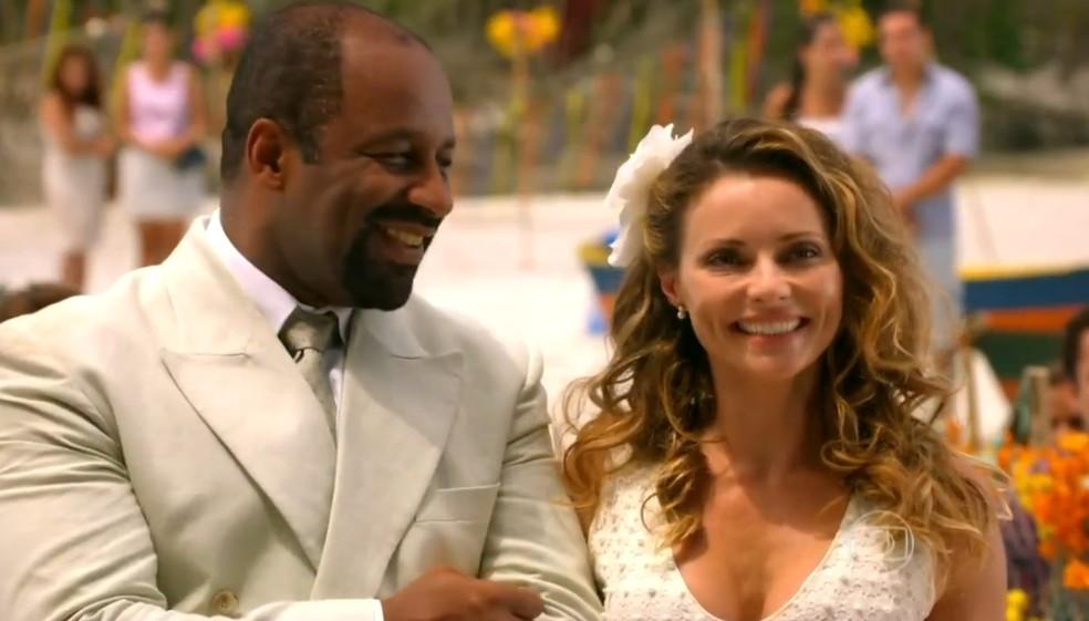 Quirino (Aílton Graça) e Doralice (Rita Guedes) se casam na praia, em 'Flor do Caribe' — Foto: Globo
