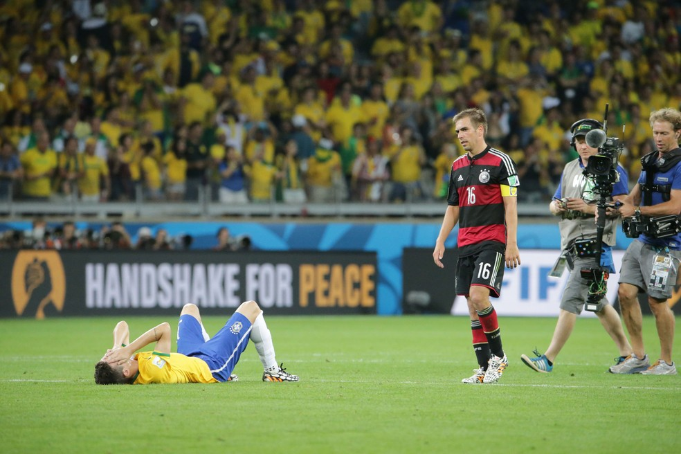 O jogador Oscar (e), da seleção do Brasil, ao lado do alemão Lahm, desaba e chora ao final da partida entre Brasil x Alemanha onde a equipe brasileira foi goleada por 7 a 1 no Estádio do Mineirão, pelas semifinais da Copa do Mundo 2014. (Foto: Estadão Conteúdo/Arquivo)