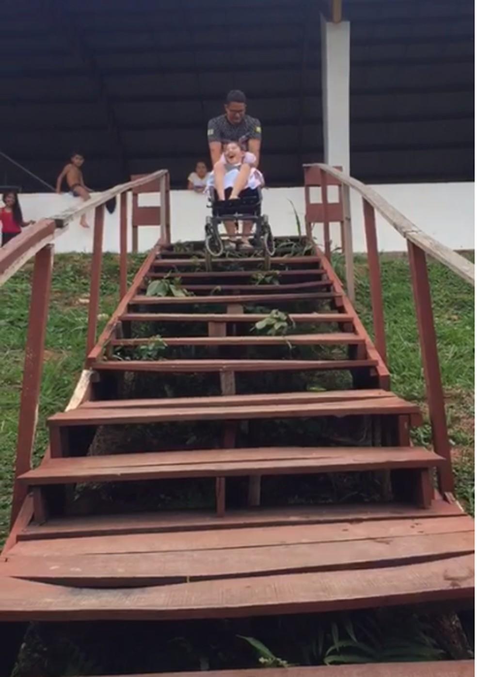 Pai e filha descem escada de acesso à quadra de escola — Foto: Reprodução