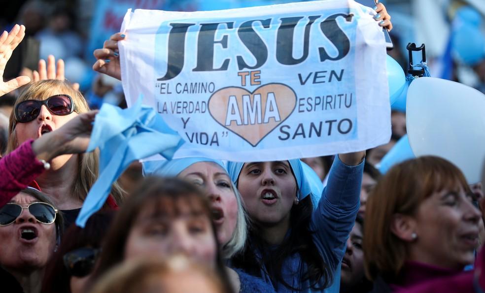 Manifestante contrária ao aborto exibe cartaz com lemas religiosos na Argentina (Foto: Agustin Marcarian/Reuters)