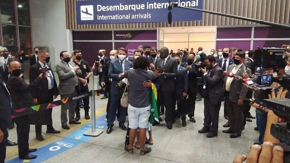 Motorista Robson chega ao Rio e abraça a mãe após 2 anos preso na Rússia. O presidente Jair Bolsonaro e comissão aplaudem a cena — Foto: Nicolás Satriano/G1