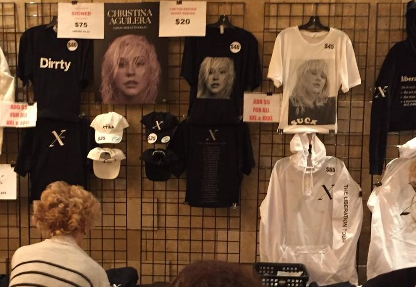O aviso na banca dos shows de Christina Aguilera avisando a taxa extra de US$ 5 por camisas plus size (Foto: Twitter)
