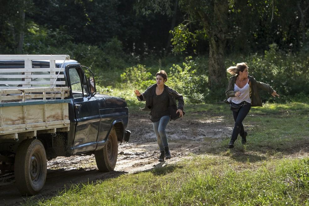 Manuela e a mãe correm para a caçamba de um caminhão (Foto: Globo/João Cotta)