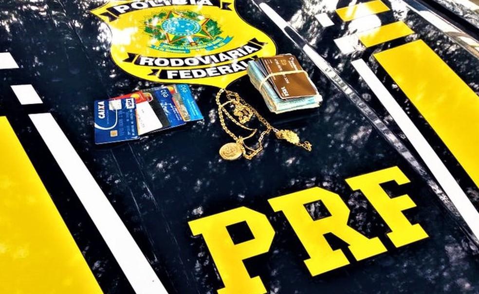 Com a dupla, foram encontrados dinheiro, algumas cédulas de dólares e euros, jóias, e 14 cartões de crédito.  — Foto: Divulgação/PRF