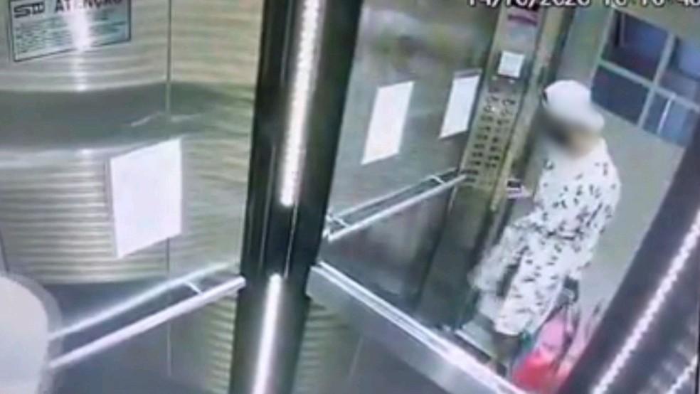 Vestindo roupão de banho de vítima e carregando sacola com objetos de valor, invasor tira foto em elevador de edifício — Foto: Reprodução/Praia Grande Mil Grau
