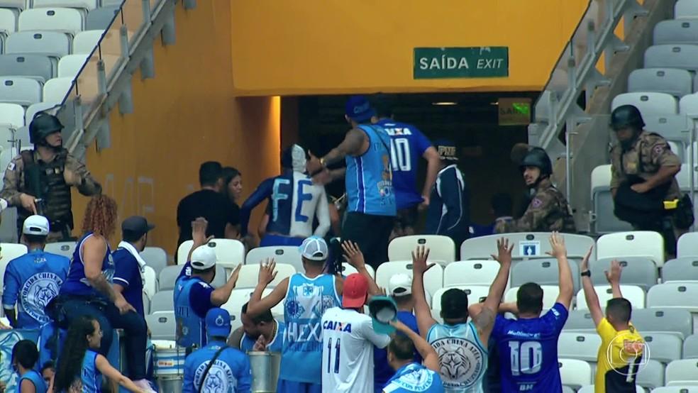 Um grupo de torcedores organizados do Cruzeiro foi mantido na arquibancada do Mineirão por policiais, enquanto os demais torcedores foram ordenados a evacuar o espaço, após o árbitro decretar o encerramento da partida entre Cruzeiro e Palmeiras — Foto: Reprodução/TV Globo