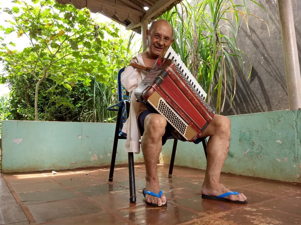 Abel Barbosa da Silva, de 77 anos, tocando na varanda da casa onde mora no Jardim Alvorada, em Maringá, no norte do Paraná. (Foto: Ederson Hising/G1 PR)