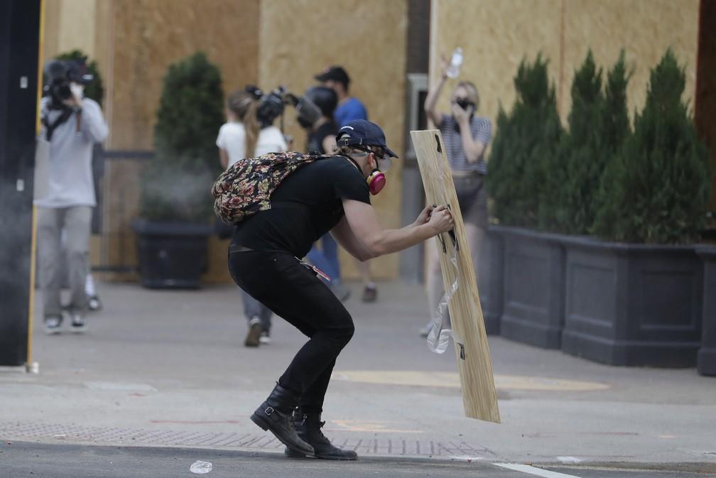 Manifestante usa tábua para se proteger de gás lacrimogêneo lançado pela polícia durante protestos em Louisville, no Kentucky, no sábado (30), pelas mortes de George Floyd e Breonna Taylor. — Foto: Darron Cummings/AP