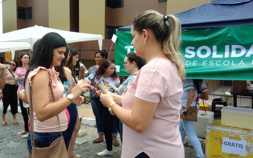 Voluntários entregam água e canetas a alunos de escolas públicas de Campina Grande em tenda solidária montada na Uninassau — Foto: Thereza Bevilacqua/Divulgação