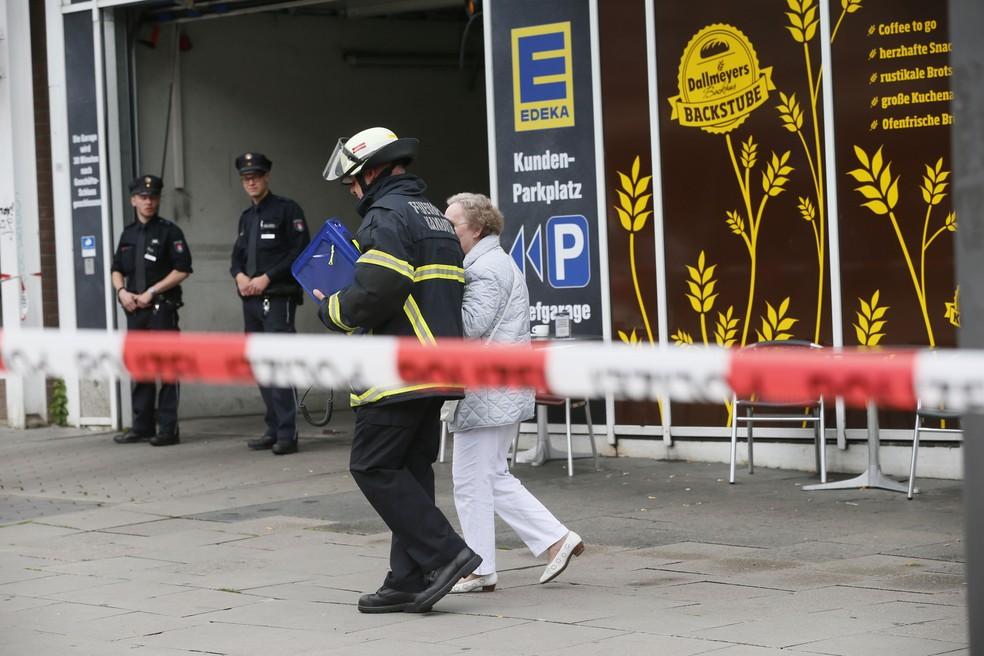 Idosa é acompanhada por um bombeiro após um ataque com faca em um supermercado em Hamburgo, na Alemanha, nesta sexta-feira (28)  (Foto: Paul Weidenbaum/ AP)