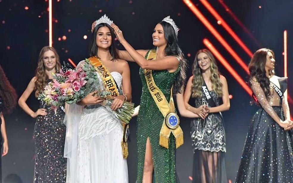 A nova Miss Brasil recebeu uma coroa em ouro branco, cravejada de pedras e uma esmeralda, avaliada em R% 52 mil, das mãos da amazonense Mayra Dias, Miss Brasil 2018 — Foto: Reprodução / Facebook / Miss Brasil BE Emotion
