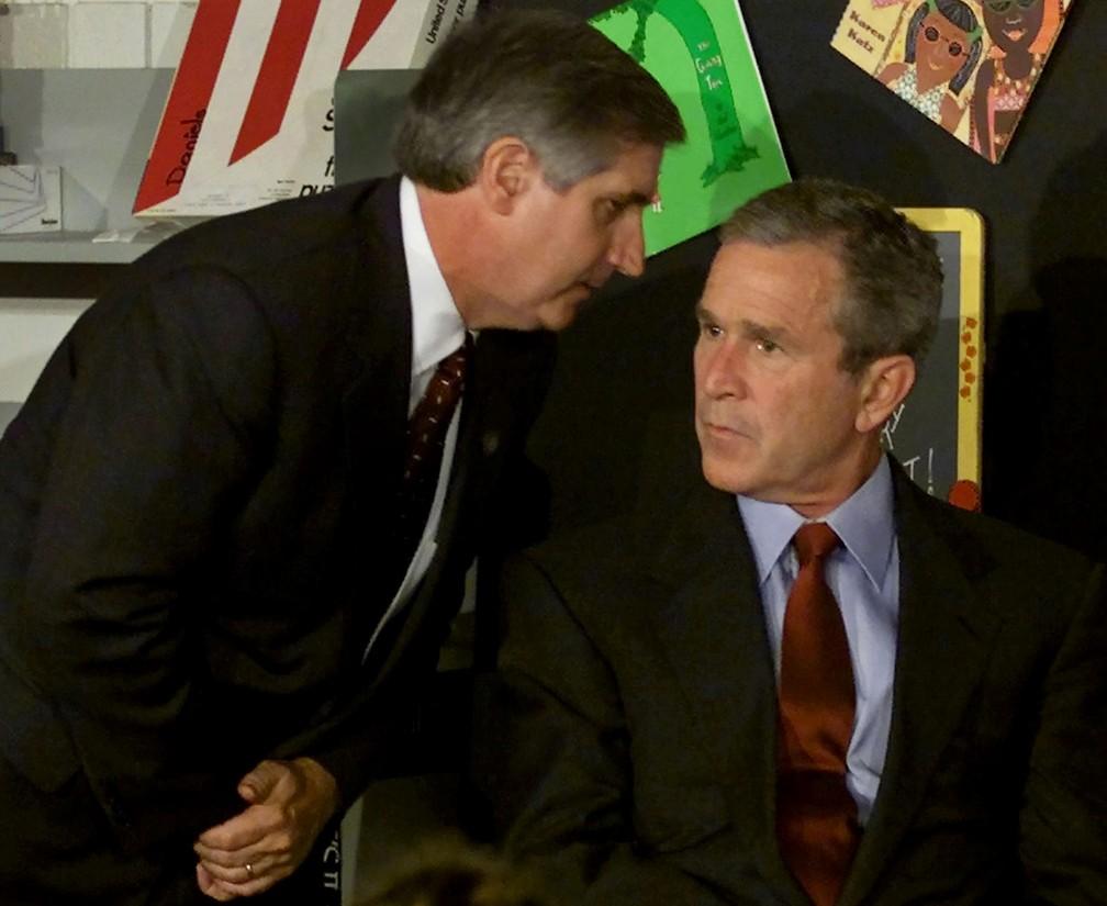 O então presidente dos EUA, George W. Bush, é informado do segundo avião a colidir com o World Trade Center por seu chefe de gabinete, Andrew Card, enquanto participa de uma leitura com crianças numa escola em Sarasota, na Flórida — Foto: Win McNamee/Reuters/Arquivo