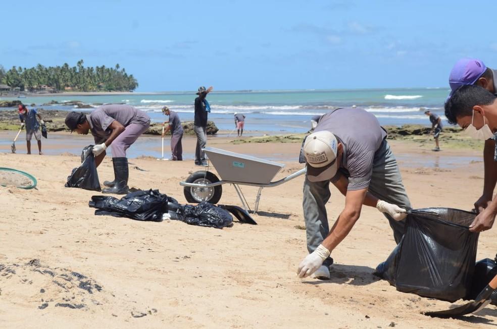 Presos fazem trabalho de limpeza das praias alagoanas atingidas por manchas de óleo — Foto: Ascom/Seris