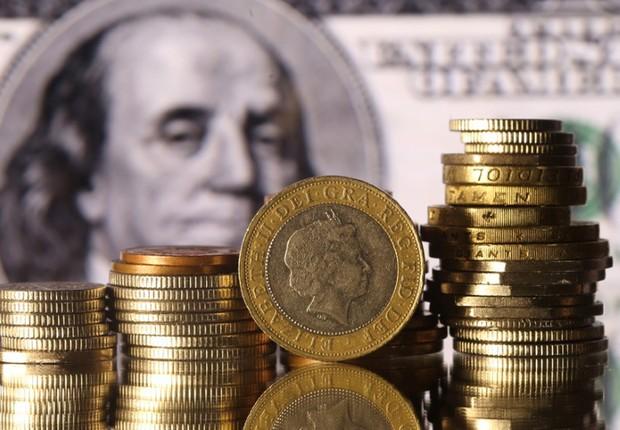 Moedas norte-americanas diante de nota de dólar ; dólares ; câmbio ;  (Foto: Dado Ruvic/Ilustração/Reuters)