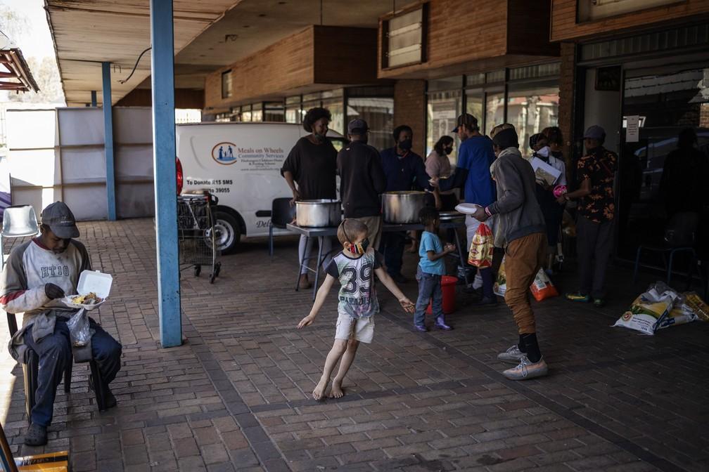 Uma criança corre enquanto pessoas fazem fila para receber refeições quentes em uma distribuição de alimentos da organização Meals on Wheels em Brapkan, na África do Sul — Foto: Michele Spatari/AFP