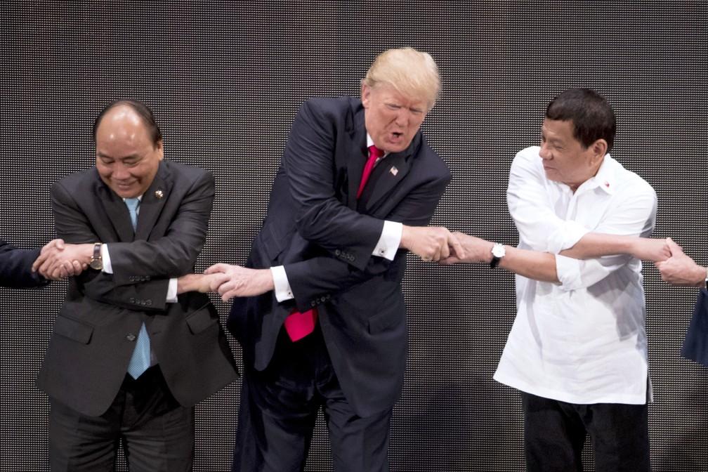 -  Donald Trump cumprimenta o primeiro-ministro do Vietnã, Nguyen Xuan Phuc, à sua direita, e o presidente filipino, Rodrigo Duterte, à sua esquerda, na