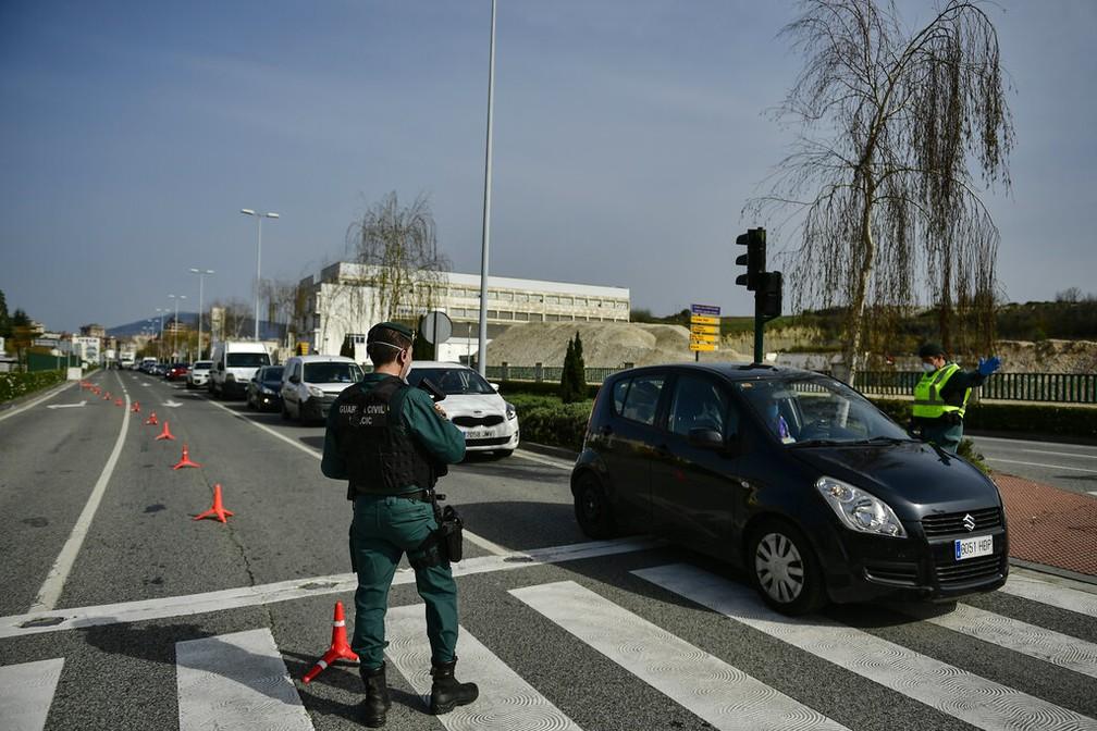 Em Pamplona, norte da Espanha, guardas só permitem a saída de pessoas autorizadas com documentação — Foto: Alvaro Barrientos/AP Photo
