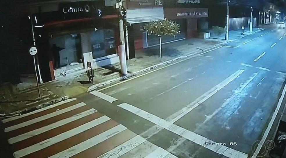 Em uma das imagens é possível ver o criminoso atirando de dentro de uma loja no centro de Ourinhos  — Foto: TV TEM/ Reprodução