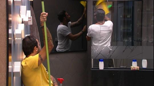 Observado por Vinicius, Gustavo limpa o banheiro