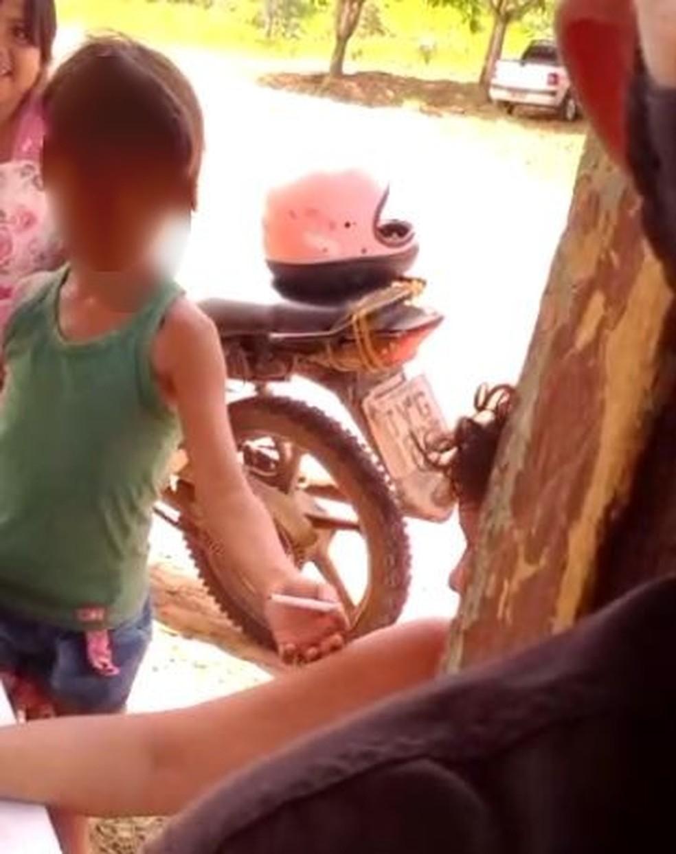 Criança entrega cigarro para a mãe após enrolar— Foto: Reprodução