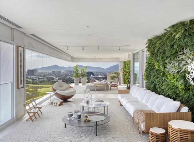 A varanda fechada tem décor assinado pela designer Fernanda Pessoa de Queiroz e jardim vertical de Carmen Mouro com 5 m x 3 m  de extensão (Foto: Juliano Colodetti/MCA Estúdio/Divulgação )