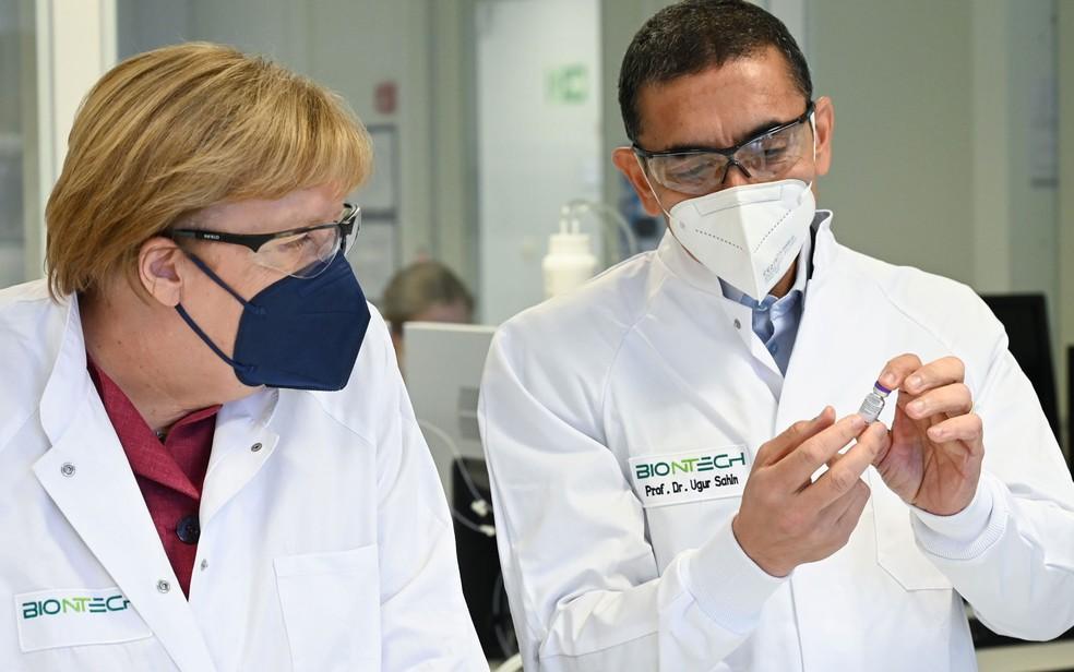 O CEO e co-fundador do BioNTech, Ugur Sahin, e a primeira-ministra da Alemanha, Angela Merkel, visitam a área de produção de vacina contra Covid-19 do laboratório em Marburg, no dia 19 de agosto — Foto: Arne Dedert/Pool via Reuters