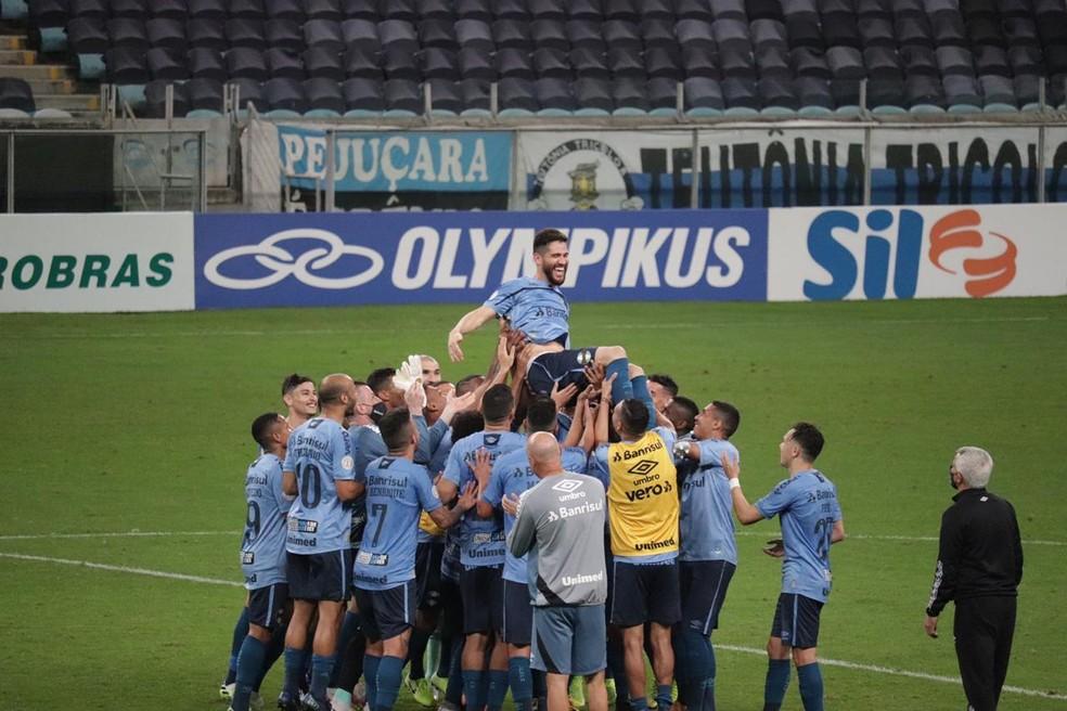 Marcelo Oliveira é erguido pelos companheiros no gramado da Arena — Foto: Lucas Bubols / ge