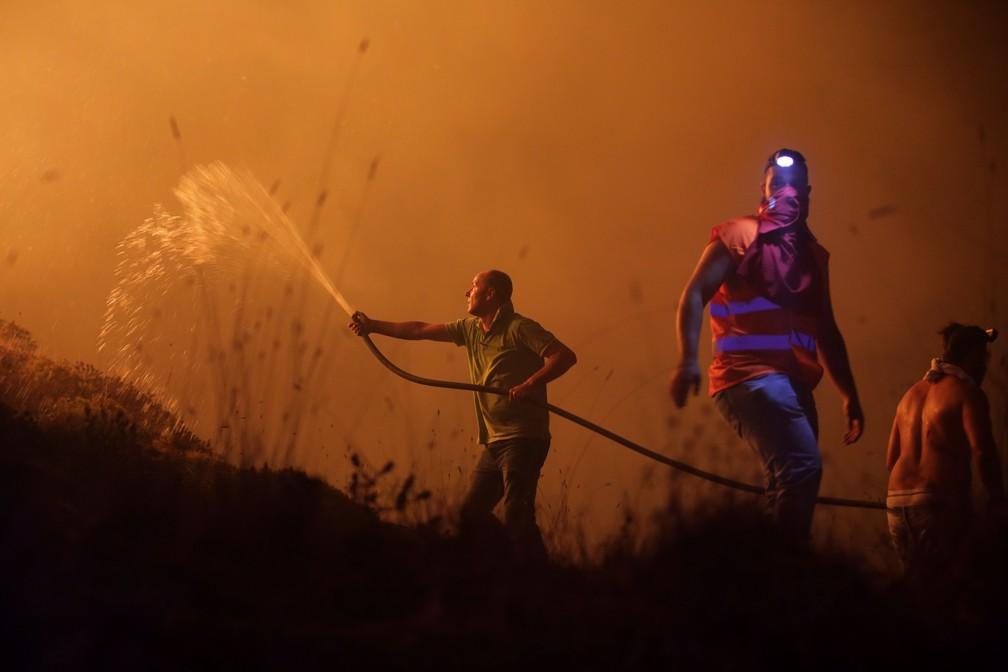 Voluntários combatem o incêndio que avançava sobre casas da região de Obidos, na madrugada desta segunda-feira (16) (Foto: Armando Franca/ AP)
