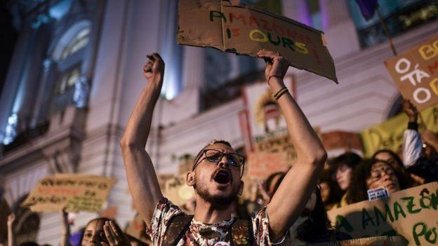 Ativista protesta, no Rio, contra a ineficácia do governo Bolsonaro no combate aos incêndios na Amazônia (Foto: MAURO PIMENTEL/AFP/ Via BBC News Brasil)