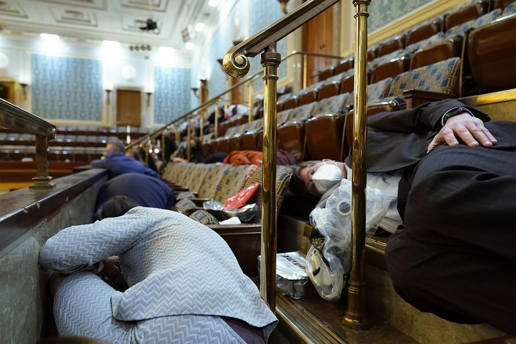 Pessoas se escondem em galeria do Capitólio durante invasão de apoiadores de Donald Trump — Foto: Andrew Harnik/AP