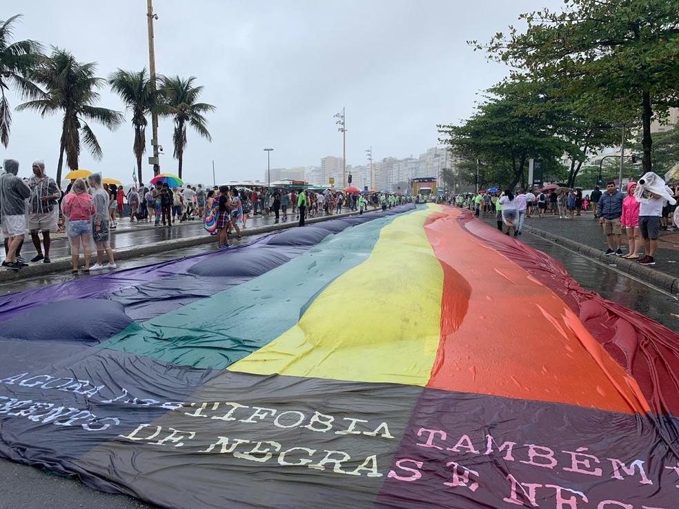 Mesmo sob chuva, faixa com as cores do arco-íris é estendida sobre a Avenida Atlântica, em Copacabana, para a 24ª edição da Parada LGBTI — Foto: Matheus Rodrigues/G1