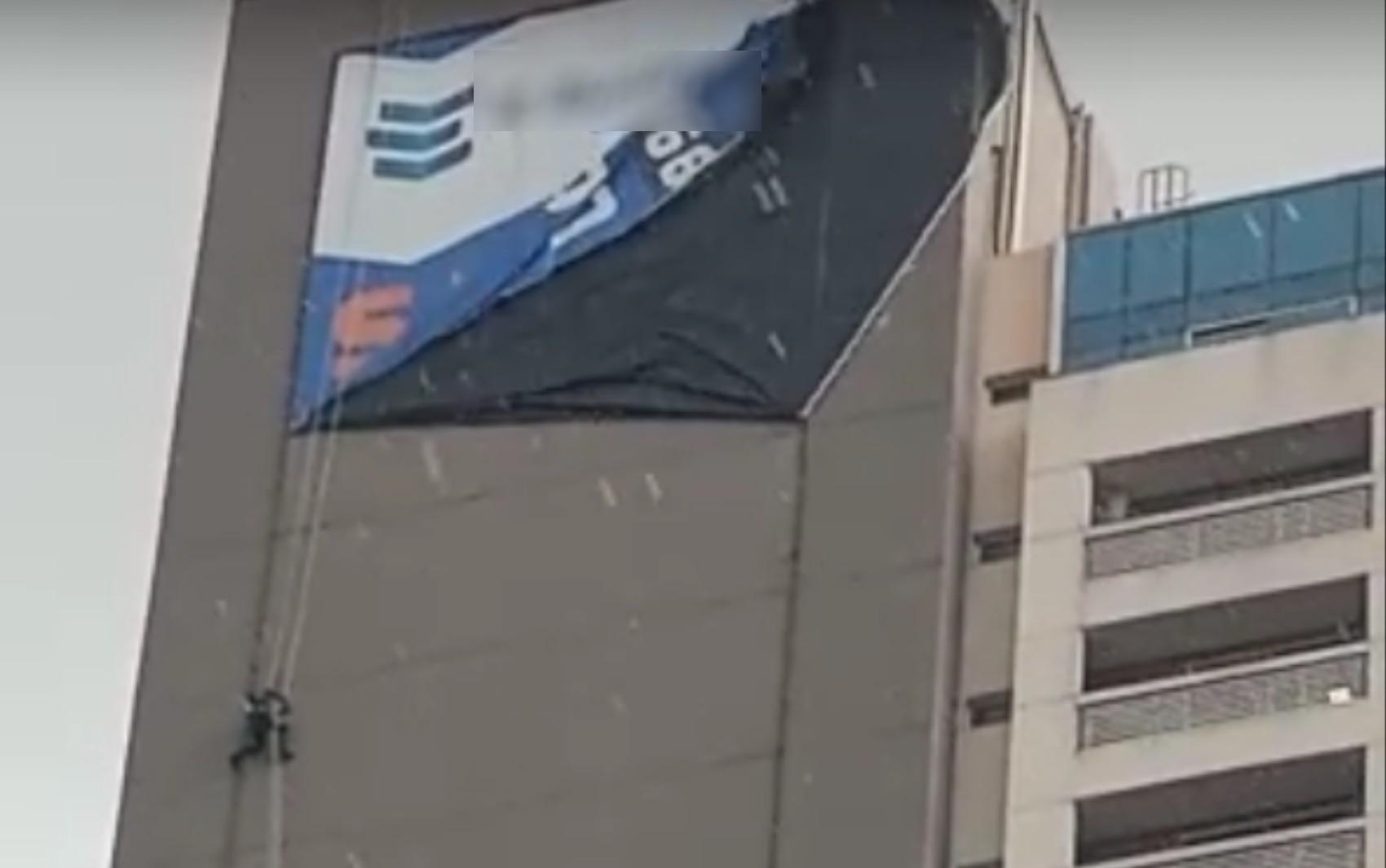 Temporal deixa trabalhador pendurado em fachada de prédio enquanto instalava lona, em Aparecida de Goiânia