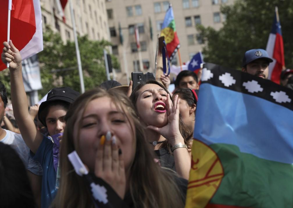 Com bandeiras do Chile e Mapuche, manifestantes ocupam as ruas de Santiago neste sábado (26) — Foto: Rodrigo Abd/Reuters