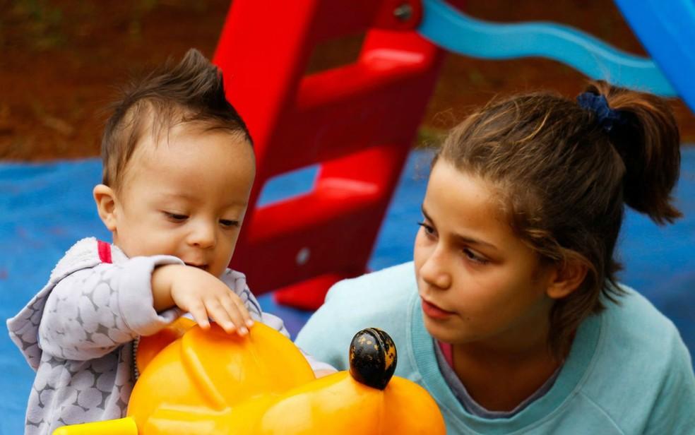 Bebê com síndrome de Down brinca com menina durante CaminhaDown em Brasília, no Parque da Cidade — Foto: Gi Salles/Divulgação
