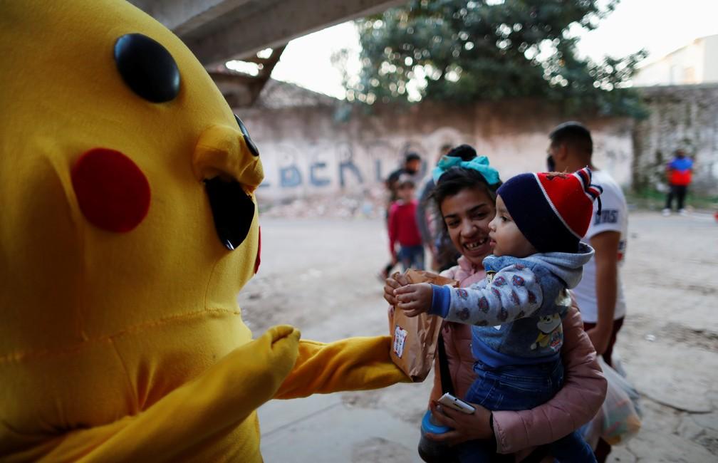 Voluntário vestido de Pikachu entrega doces a criança em Buenos Aires, na Argentina, no domingo (16) — Foto: Agustin Marcarian/Reuters
