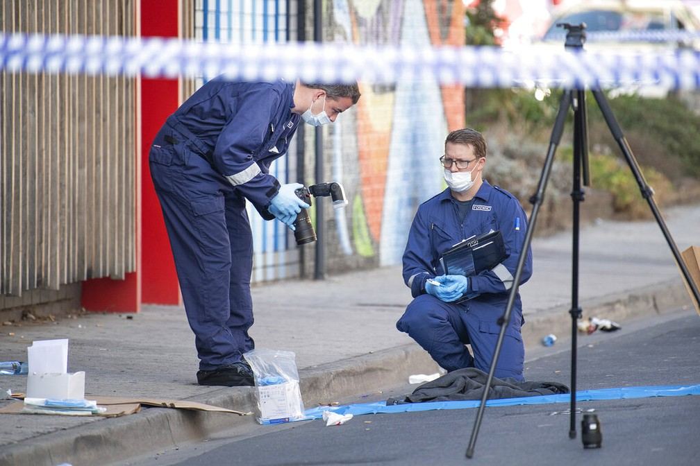 Especialistas forenses examinam objetos do lado de fora de casa noturna após tiroteio em Melbourne, na Austrália, neste domingo. — Foto: Ellen Smith / ASSOCIATED PRESS