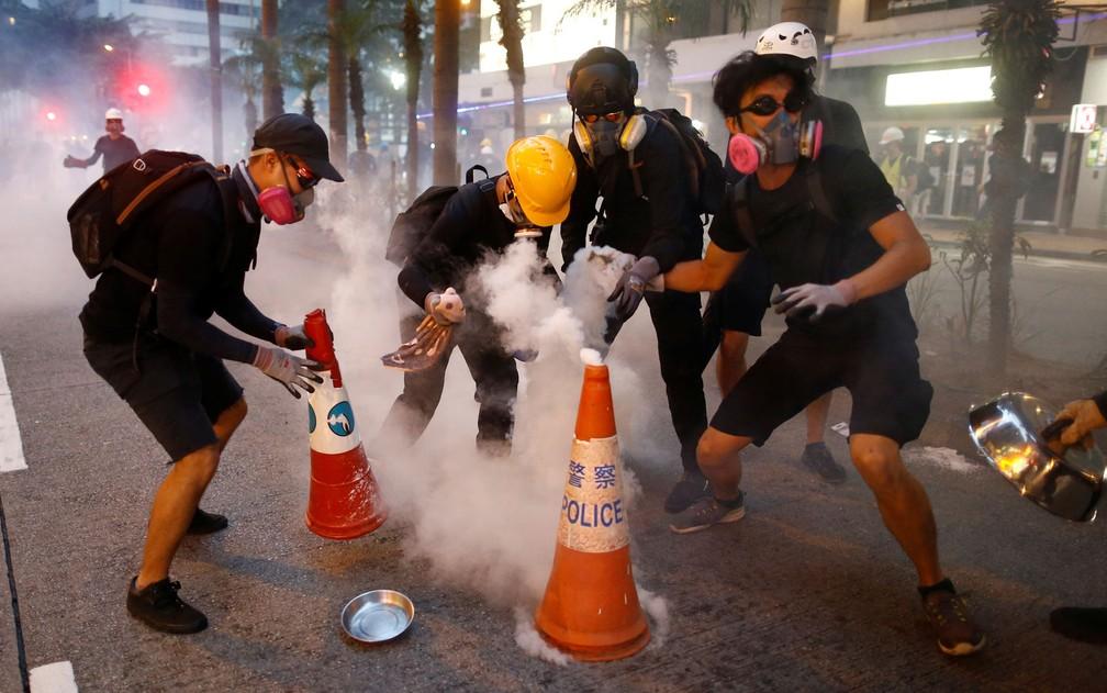 O mobiliário urbano de Hong Kong ganha novas funções nas mãos dos manifestantes: sinalizações de ruam servem para abafar efeito de bombas de gás lacrimogêneo — Foto: Reuters/Thomas Peter