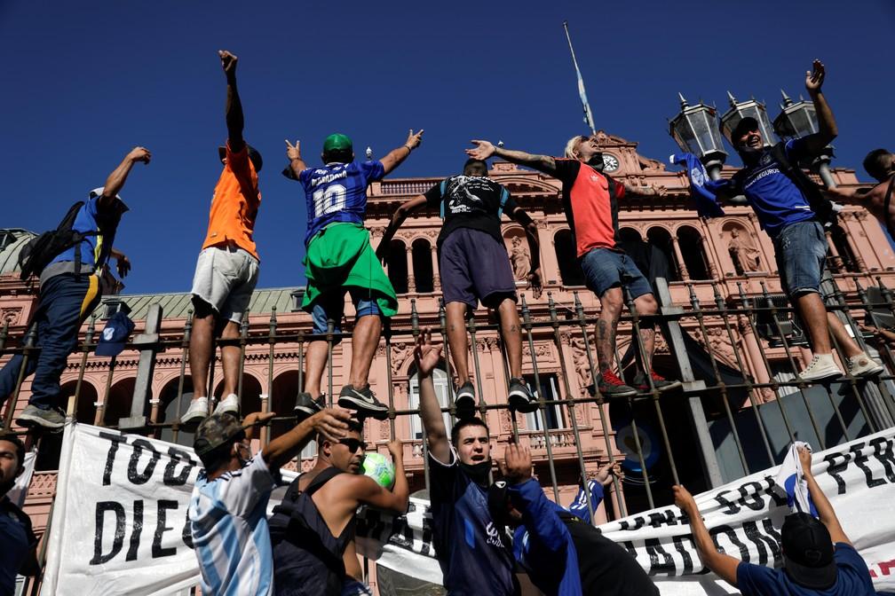 Torcedores sobem nas grades da Casa Rosada antes da saída do carro com o corpo de Maradona — Foto: Reuters