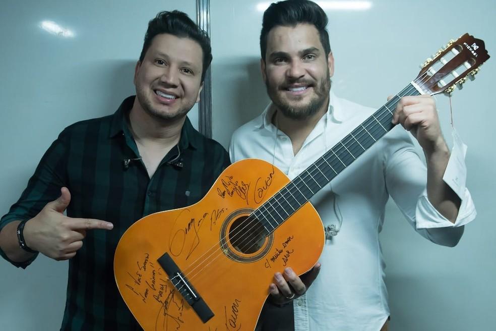 Cleber & Cauan assinaram o violão que será leiloado em prol do hospital Hélio Angotti — Foto: ANDRÉ SANTOS