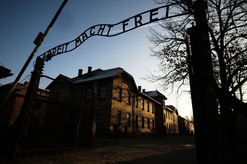 Sol ilumina prédios atrás da entrada do antigo campo de extermínio nazista de Auschwitz-Birkenau em Oswiecim, na Polônia, nesta sexta-feira (6)  — Foto: Markus Schreiber/AP