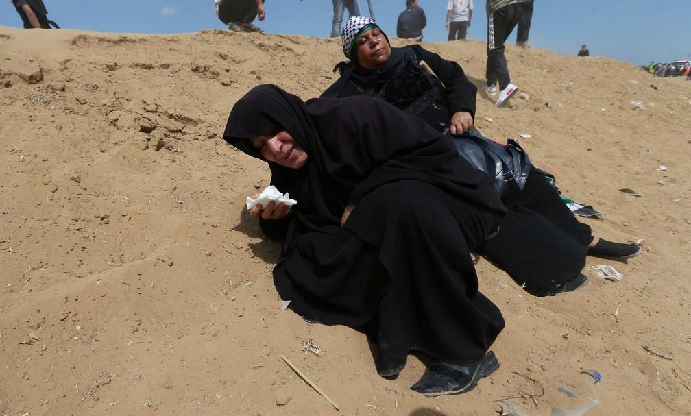 Palestinas reagem aos efeitos de bombas de gás lacrimogêneo lançadas contra a Faixa de Gaza durante confronto nesta segunda-feira (14) (Foto: Ibraheem Abu Mustafa/Reuters)